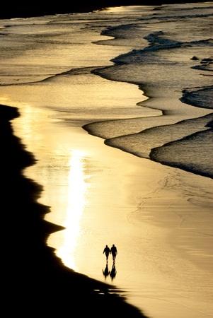 strand australie: silhouet van een paar lopen op het strand met zonsondergang licht