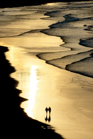 silhouette of a couple walking on the beach with sunset light photo