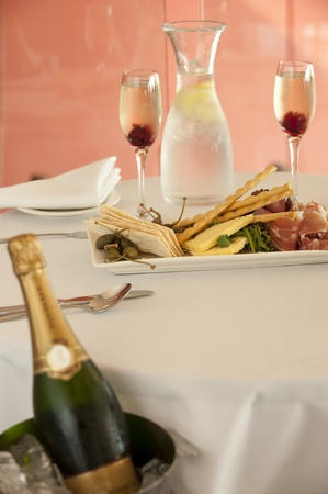 entree: pastry crackers entree with roast beef,prosciutto,rocket and salami and champagne in ice bucket Stock Photo