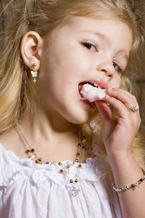 beautifull little blonde girl portrait with silver jewellery eating a cotton candy and looking at the camera photo