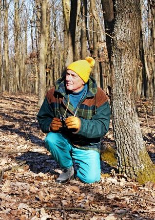 Senior man is looking the wildlife in winter forest Stock Photo - 12053759