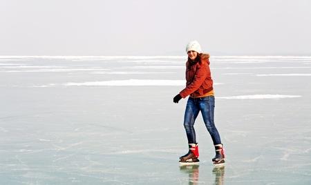 Happy teenager girl is skating on frozen Lake Balaton,Hungary photo