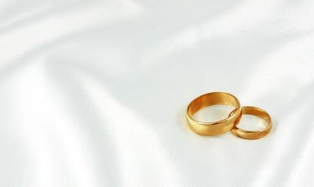 Golden wedding rings on white silk
