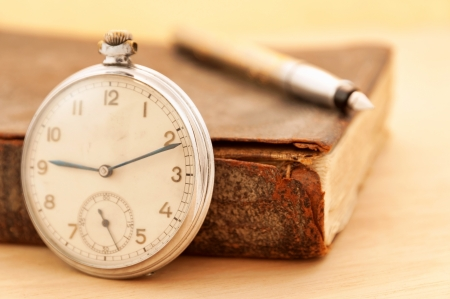 Old clock with vintage book photo