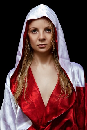 red bathrobe: Young pretty woman in red and white silk bathrobe with wet hairs isolated on the black background Stock Photo