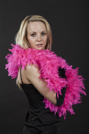 black boa: Young attractive woman with pink boa isolated on the black background