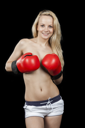Naked girl: Young sexy smiling woman in white shorts, covering her breast with boxing gloves, studio portrait. Stock Photo