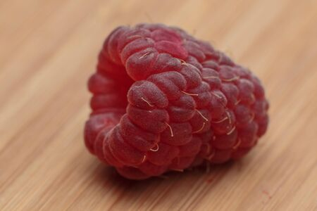extremely: Extremely close-up view of raspberry lying on the wooden kitchen board
