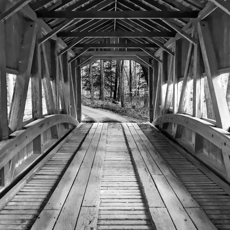 Interior of an old historical vintage covered wooden bridge crossing a river or creek leading out into woodland, monochrome image Stock Photo