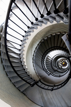 Architectural pattern of a spiral staircase viewed from the top curving away downwards in a receding helix, monochrome image Archivio Fotografico