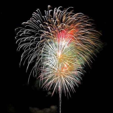 guy fawkes night: Fuochi d'artificio colorati vengono visualizzati con rottura razzi in una pioggia di scintille e sentieri di fuoco in un cielo notturno concettuale di una festa di anniversario, Capodanno o Independence Day