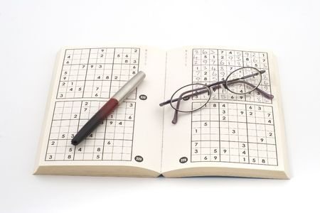 pair of glasses and pen on open sudoku book