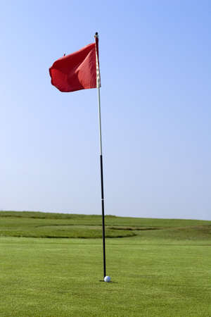 A putting green with flag and golf ball photo