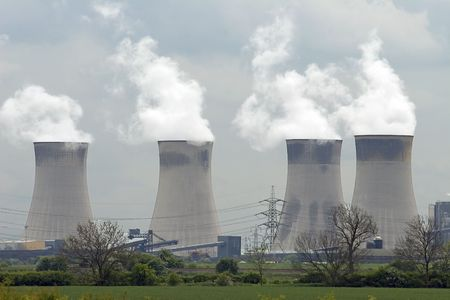A coal fired power station with smoke pouring from cooling towers