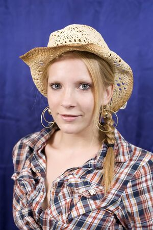 An attrative blonde teen in check shirt and straw hat