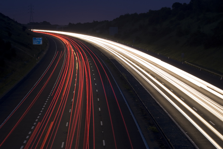 A motorway by night with tails caused by car lights