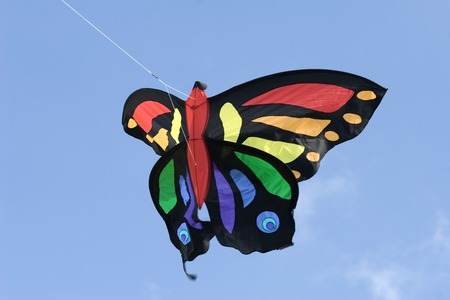 A colorful butterfly shaped kite flying in a blue sky Stock Photo