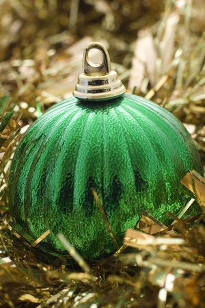 A green christmas decoration with gold tinsel