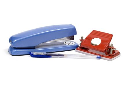 A stapler, hole punch and pen on a white background