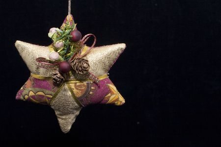 A star shaped christmas decoration on a black background with copy space to one side