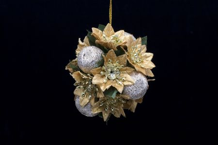 A gold and silver christmas decoration photographed against a black background