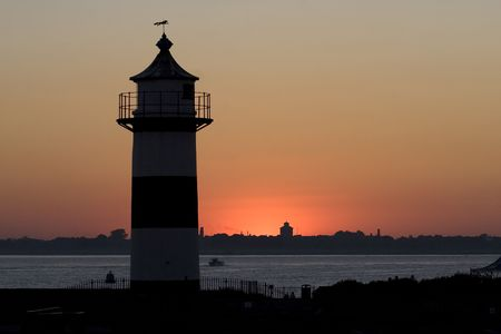 A silhouette of a lighthouse at dusk Stock Photo