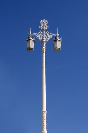 An old fashioned lamp post photographed against a bright blue sky Stock Photo