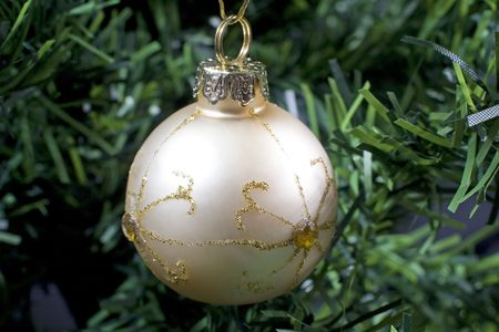 a gold coloured christmas bauble hanging in a tree