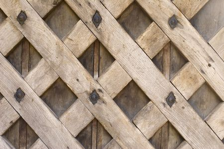 A wooden trellis pattern on an old gate