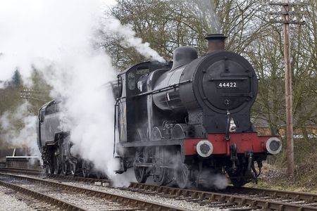 A steam engine pulls into a railway station