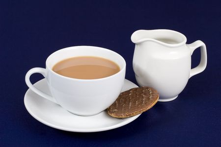 A cup of tea with a chocolate biscuit and milk jug