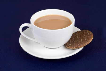 A cup of tea with a chocolate biscuit in the saucer
