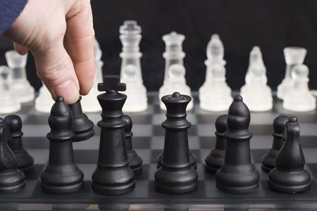 The first move in a game of chess, shallow depth of field focusing on players hand