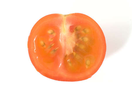 A juicy tomato sliced in half on a white background