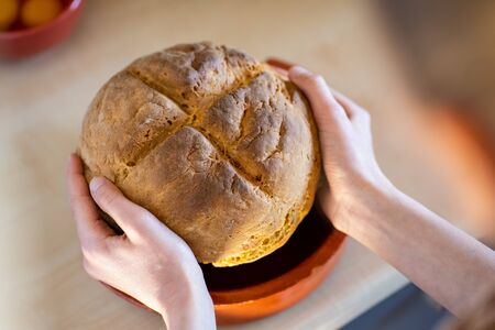 Girl hands holding freshly baked irish soda bread with cutted cross. Healthy, home made, delicious pastry.