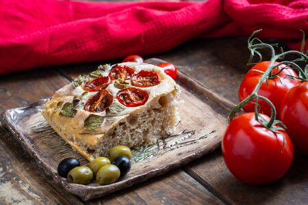 Slice of homemade, beautiful and delicious, italian focaccia on ceramic plate, on wooden table. Decoration that looks like flowers in garden is made of cherry tomatoes, olives and fresh herbs.