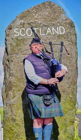Bagpiper plays music at the large stone marker at the Scottish and English Border
