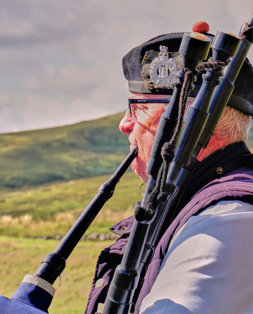 Senior male bagpiper playing in the great Scottish outdoors