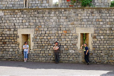 Windsor, England - Aug 2016: Three people on electronic devices stand equal distance apart in front of old stone wall 新聞圖片