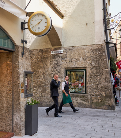 Salzburg, Austria - Aug 2018: Candid shot of two business men in work clothes walking through a scenic section of old Salzburg 新聞圖片