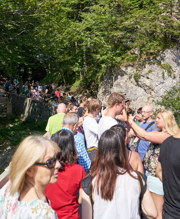 Hohenschwangau, Germany - Aug 2018: Large group of tourists crowd onto tiny Marienbrucke to get a view of Neuschwanstein Castle in Bavaria Editorial