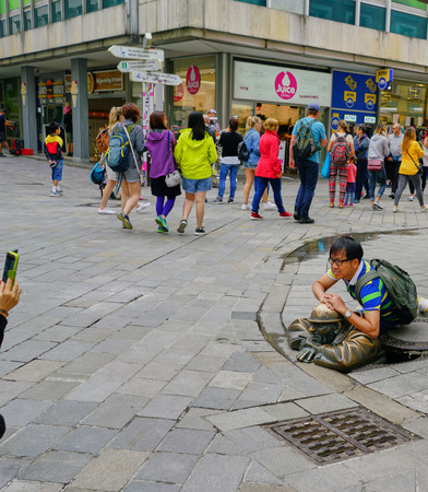 Bratislava, Slovakia - Aug 2018: Young Asian man with backpack crouches over brass sculpture of sewer worker emerging from man-hole on city streets while tourist pass by Editorial
