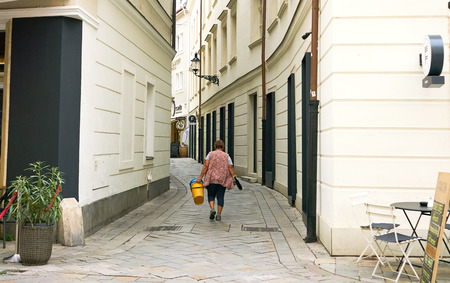 Bratislava, Slovakia - Aug 2018: Woman walks down an old lane in old town with her buckets and squeegee. Editorial