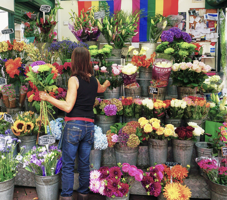 Woman tends to her outdoor  Flower Shop Street Kiosk - London, England - Aug 2017