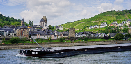 Loaded Barge pushes through the water of the Rhine River as it travels past quaint village with vineyards in the Middle Rhine, Germany