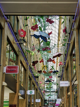Butterfly mobiles hanging from glass covered ceiling in shopping arcade in Munich Germany Editorial
