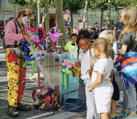 Colorful friendly clown makes balloon animals for children - Frankfurt - Aug 2016 Editorial
