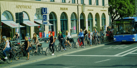 Long line up of business women on bicycles in downtown Munich Germany - Aug 2016 Editorial