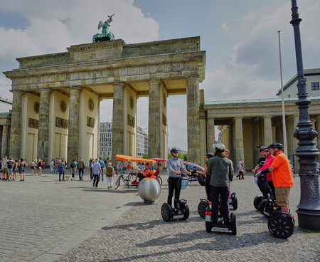 Group of people on Segways taking a break in front of the famous Brandenberg Gate in Berlin, Germany - Aug 2016