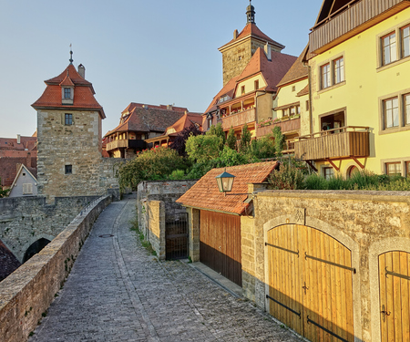 Golden sunlight on medieval buildings on the walled fortification in famous tourist destination, Rothenburg, on the Romantic Road in Germany Banco de Imagens